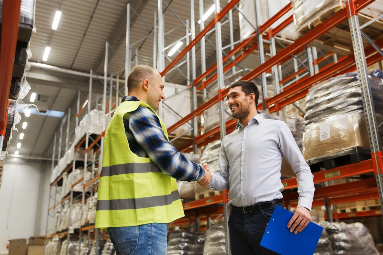 two people shaking hands in a warehouse